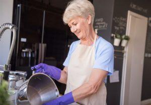 mulher idosa lavando panela